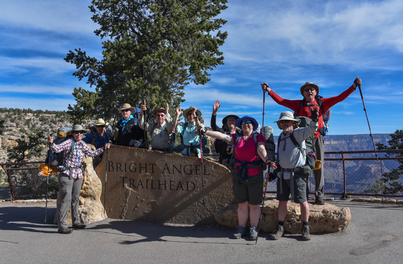 Hikers stand behind the Bright Angel Trailhead
