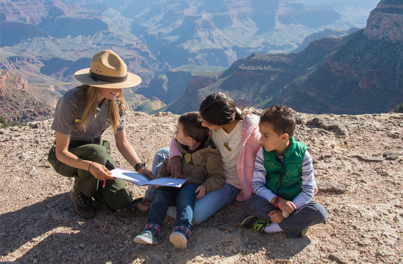 Ranger sits down on the rim of Grand Canyon with three children reading a book.