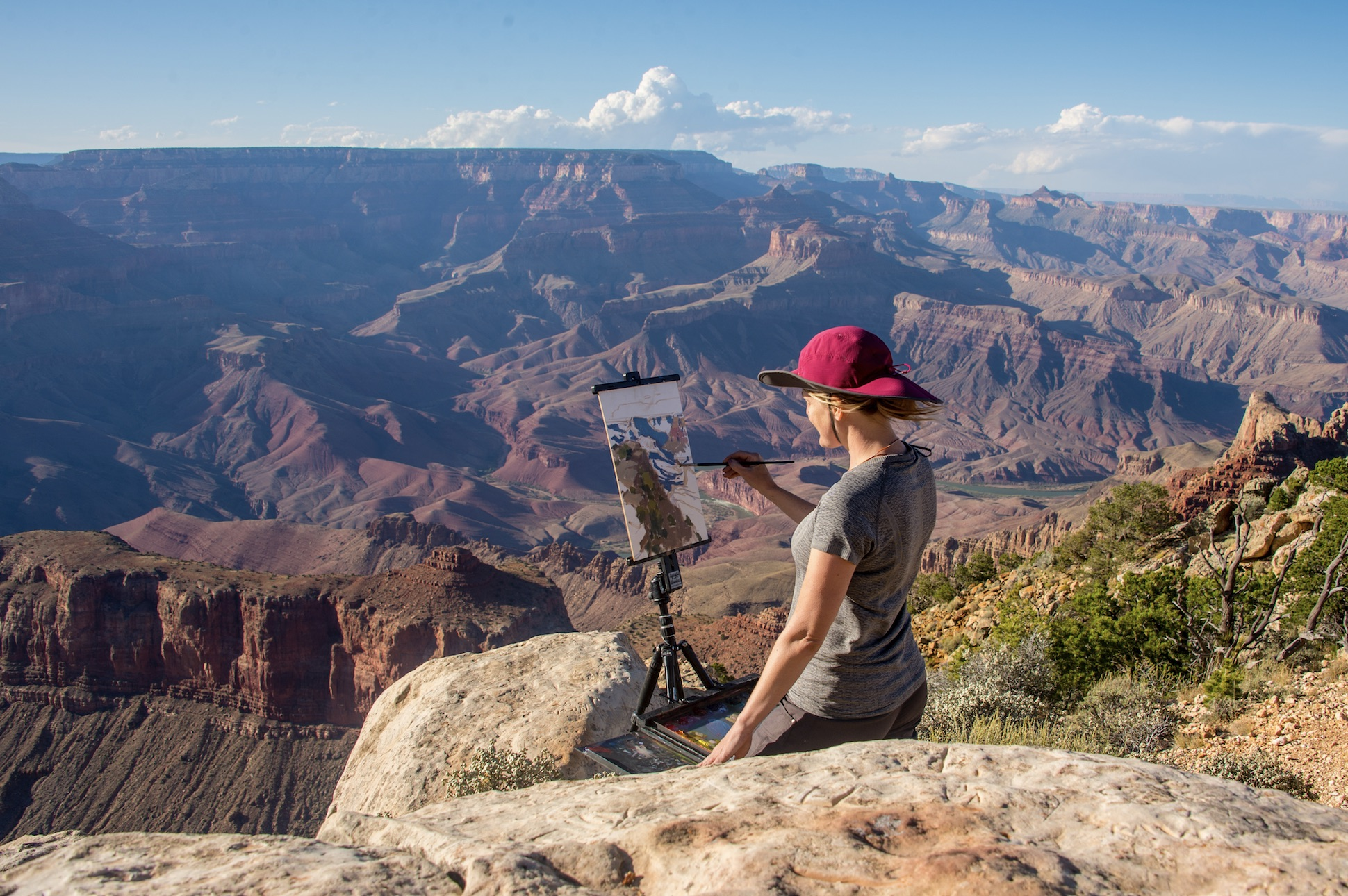 Female paints on a canvas in front of Grand Canyon