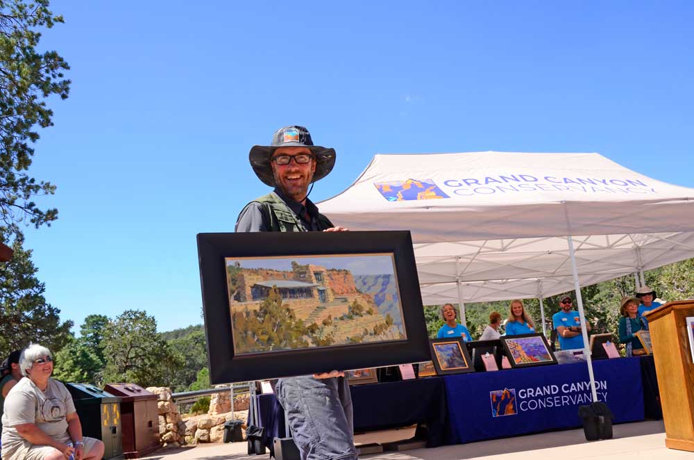 An artist holds up a painting with Grand Canyon Conservancy booth in the backdrop