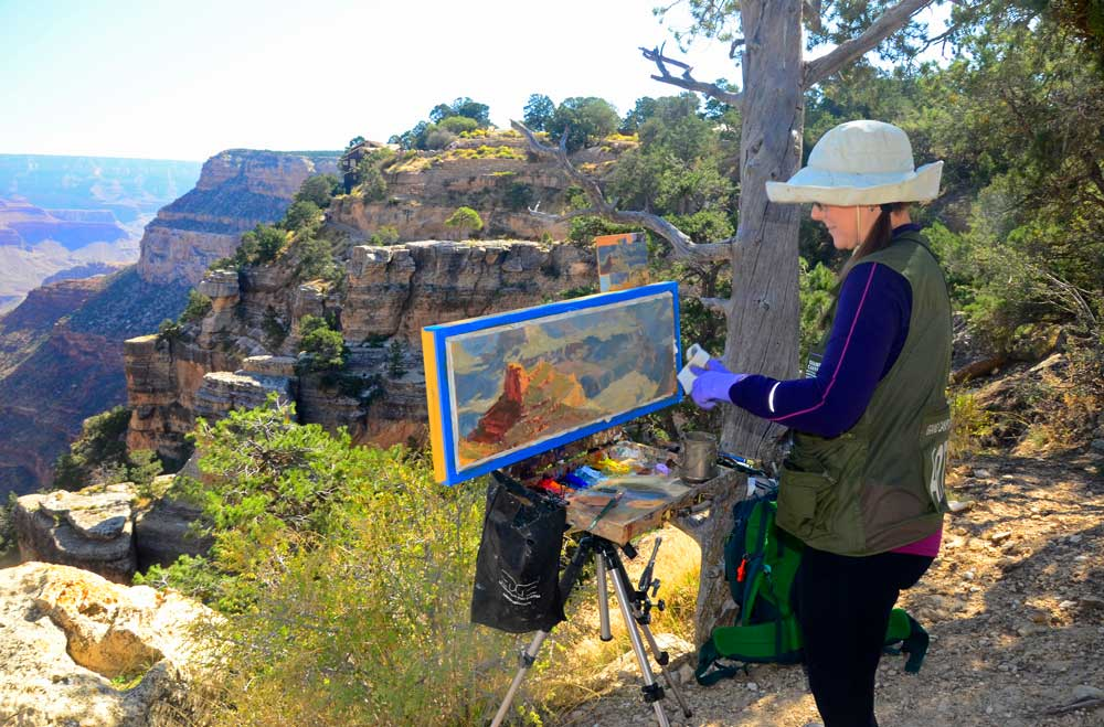 An artist puts the final touches on her painting of Grand Canyon