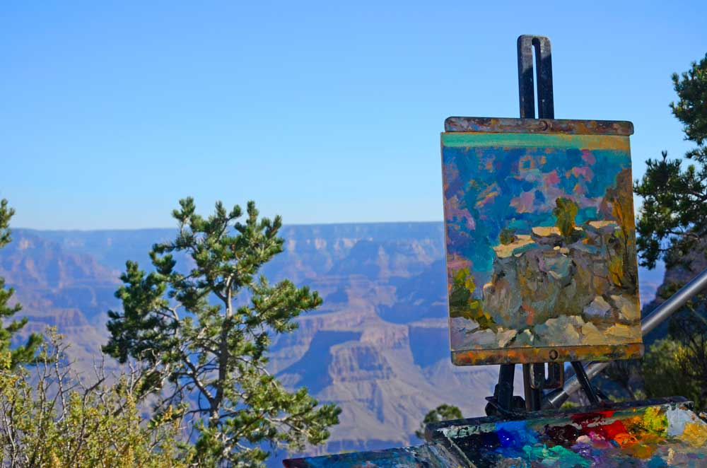 A painting on an easel stands before Grand Canyon